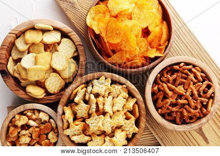 Salty snacks. Pretzels chips crackers in wooden bowls.