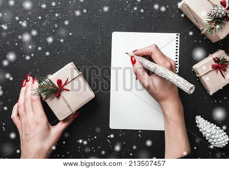 Christmas greeting card, a lady writes her wishes in a xmas ambiance. christmas ambiance