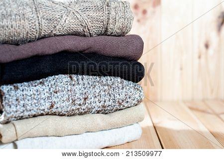 Knitted Winter Clothes And Wool Sweaters On Wood Background. Copyspace,.