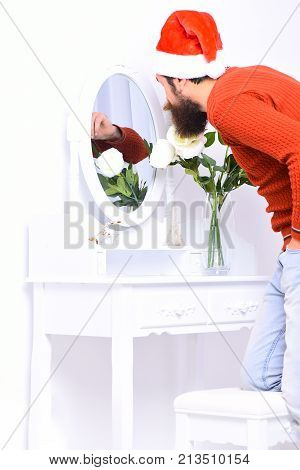 Guy Leans Down To Mirror With Flowers In Vase.