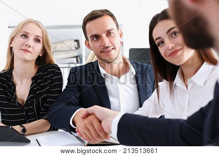 Smiling man in suit shake hands as hello in office portrait. Friend welcome mediation offer positive introduction greet or thanks gesture summit participate approval strike arm bargain concept