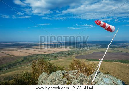 Flying windsock wind vane on mountine backgound, Check wind speed for paragliding in mountains