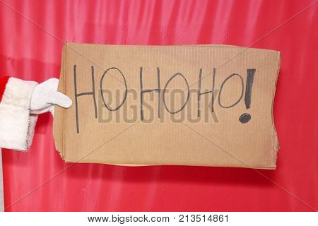 Santa Claus Sign. Santa Claus arm and hand holds a Cardboard Sign with messages against a red background.