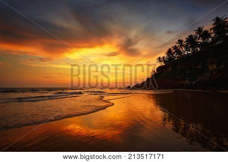 Sunset on Varkala beach popular tourist destination in Kerala state, South India