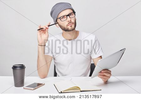 Indoor shot of confident strict young male boss or employer has trendy hairstyle and beard wears glasses and t-shirt preparing business report using modern laptop computer keeping documents pen.