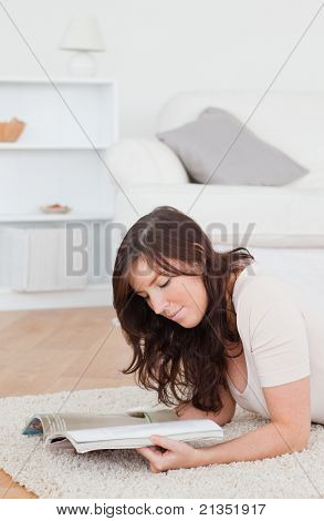 Junge hübsche Frau, die eine Zeitschrift lesen, beim liegen auf dem Teppich im Wohnzimmer