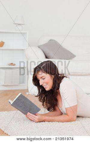Junge schöne Frauen, die ein Buch zu lesen, beim liegen auf dem Teppich im Wohnzimmer