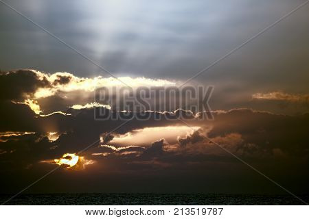 Awakening. Soft spiritual image of sunrise or sunset over tropical sea. Turbulent uncertain weather ahead over the ocean. Change in the weather as clouds form in the twilight sky.