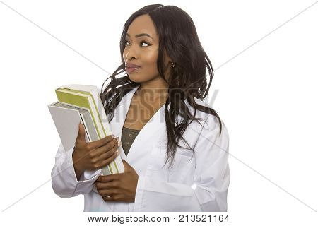 Black female wearing a lab coat with books is a student of STEM meaning Science Technology Engineering and Mathematics. She is isolated on a white background.