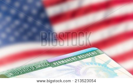 United States of America permanent resident cards green card with US flag in the background. Legal immigration concept. Closeup with shallow depth of field.