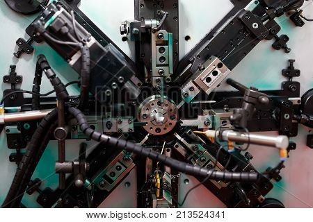 Industrial automatic spring coiling machine. Selective focus.