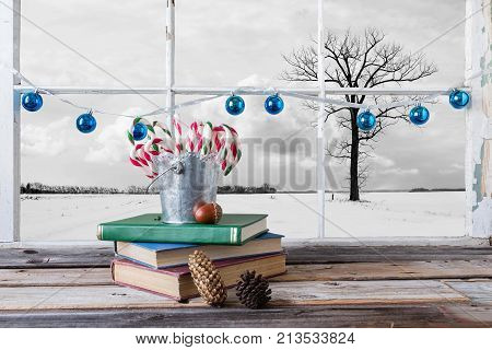 image of a tin pail sitting on top of books filled with Christmas candy canes in front of window with blue balls strung across the frame with a winter scene on the outside.