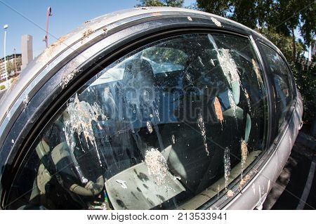 Bird droppings cover the driver's side window of a parked car in a parking lot.