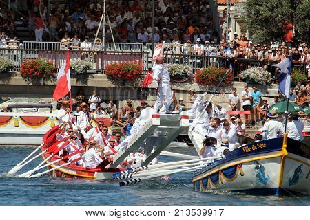 Sete, Herault, France  - Aug 21 2017: Traditional French Water Jouster Falling Into The Canal At The