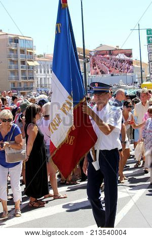 Sete, Herault, France  - Aug 21 2017: Police Officer Carrying The French Flag Or Tricoleur In The Pa