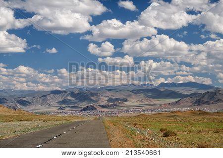 Empty Asphalt Road In Mongolia  With Mongolian Town Bayan-olgii (bayan-ulgii Or Ulgii) On Background