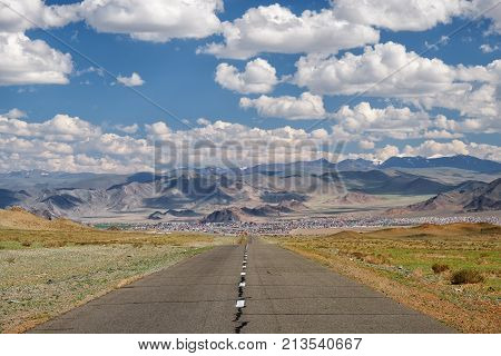 Empty Asphalt road in Mongolia with mongolian town Bayan-Olgii (Bayan-Ulgii or Ulgii) on background under blue sky