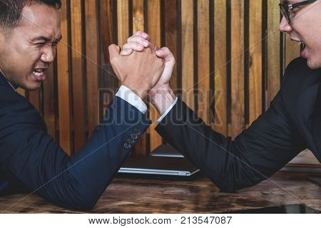 Two Businessmen arm wrestling on the desk in the office.