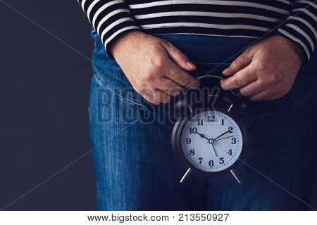Time is passing female hand holding stylish black vintage alarm clock selective focus. Concept of reproductive health control for women.