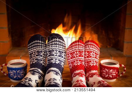 Couple In Christmas Socks Near Fireplace