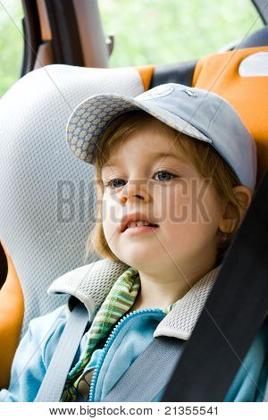 Happy Smiling Little Girl Seated In Child Seat In The Car