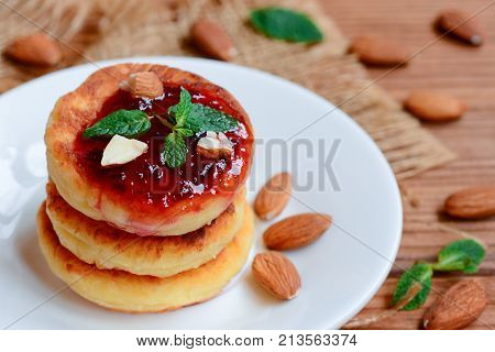 Cottage cheese pancakes. Fried cottage cheese pancakes with berry jam and almonds on a white plate. Traditional russian syrniki recipe