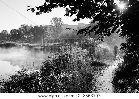 Autumn landscape in city park in black and white. Man walking on path along foggy river. Sun shines through leaves