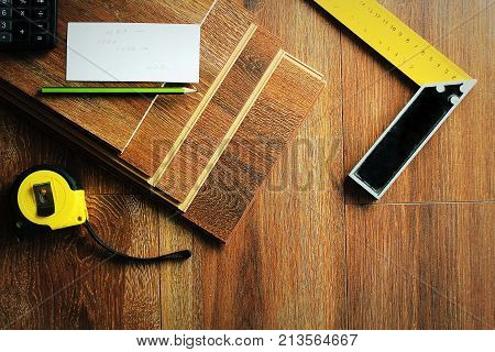 Laminate floor planks and tools on wooden background. Different carpenter tools on the laminated floor .Top view .