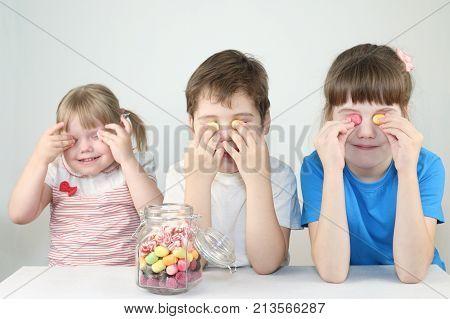 Three happy children close eyes by candies near jar on table in white studio