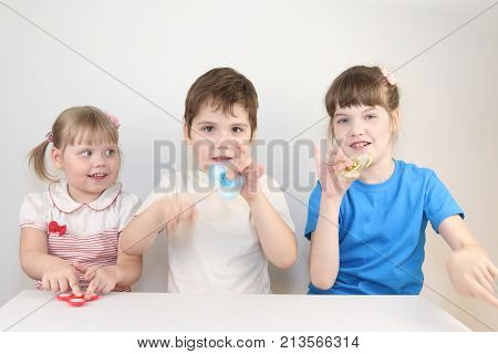 Three happy children play with spinners on table in white studio