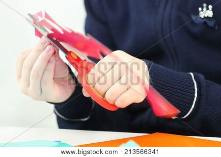 Hands of girl cutting flower from red paper for crafts close up