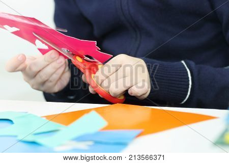 Hands of girl cutting flower from colored paper for crafts closeup