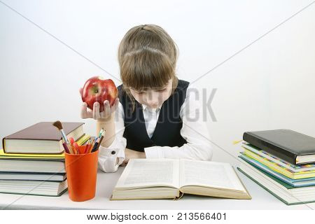 Schoolgirl in uniform reads book and eats red apple at table in studio