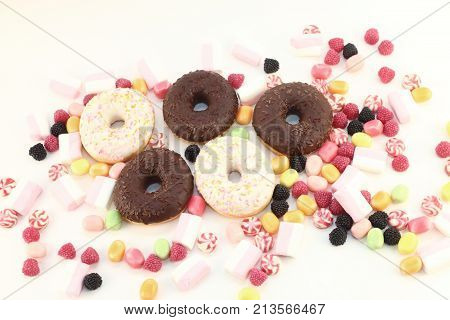 Donuts many bright candies and marshmallows on white surface top view