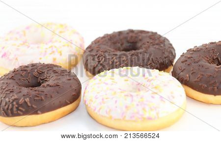 Five appetizing fresh white and chocolate donuts close up view