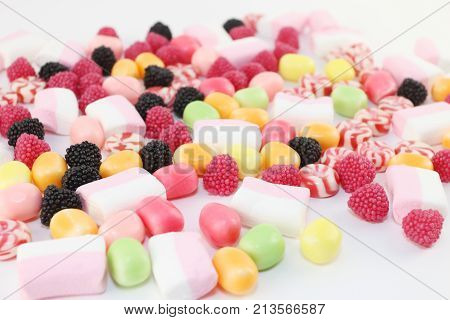 Many sweet candies and marshmallows on white surface closeup