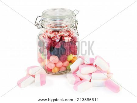 Glass jar with candies and marshmallows isolated on white background