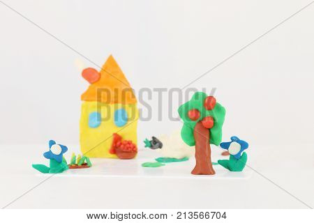 Bright house sheep flowers tree from plasticine on white table