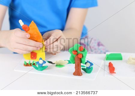 Child hands molding house tree flowers from plasticine on table in room