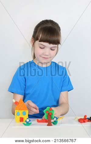 Smiling pretty girl molds toys from plasticine on table in white room