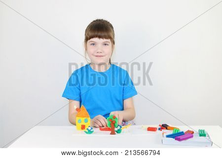 Smiling girl in blue molds house from plasticine on white table in white room