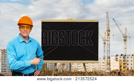 Happy smiling builder worker man in a hardhat holding in hands pointer stick and showing on a black board with copy space on construction site background with cranes. Construction plan presentation.