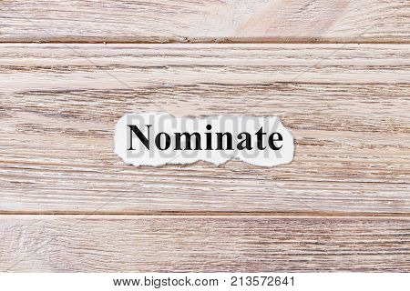 NOMINATE of the word on paper. concept. Words of NOMINATE on a wooden background.