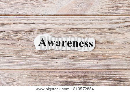 AWARENESS of the word on paper. concept. Words of AWARENESS on a wooden background.