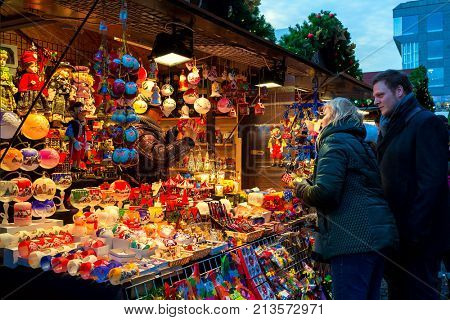PRAGE, CZECH REPUBLIC - DECEMBER 10, 2016: People buying handmade decorations at wooden kiosk  during famous traditional Christmas Market taking place each year on december in Old Town of Prague.