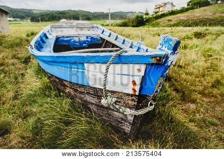Old abandoned wooden fishing boat stranded on land and grass. Weathered used vintage fishing vessel in decaying on land in Galicia Spain.