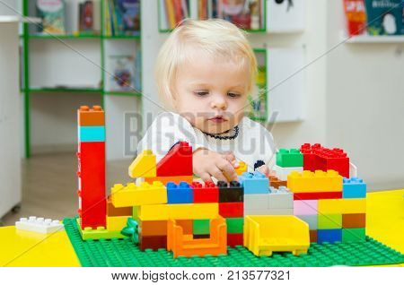 Baby Blond Girl Playing With Building Blocks