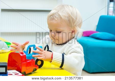 blond girl playing toy cars and building blocks