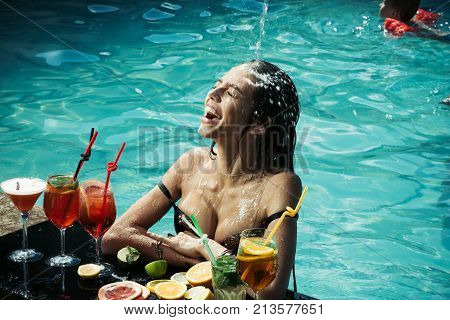 Cocktail and sexy girl in pool. Summer vacation and party. Woman with alcoholic beverage and fruit. Swimming and relax in water pool. Drink food and happiness.