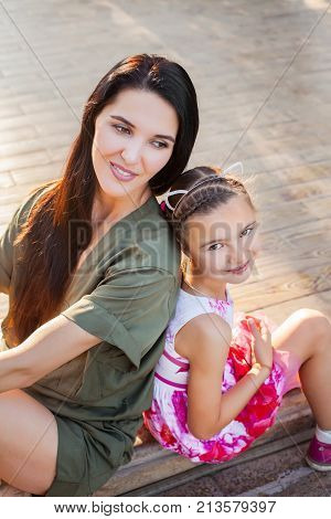 Beautiful mother and daughter sitting outdoors on steps, laughting and having fun. Concept of happy family